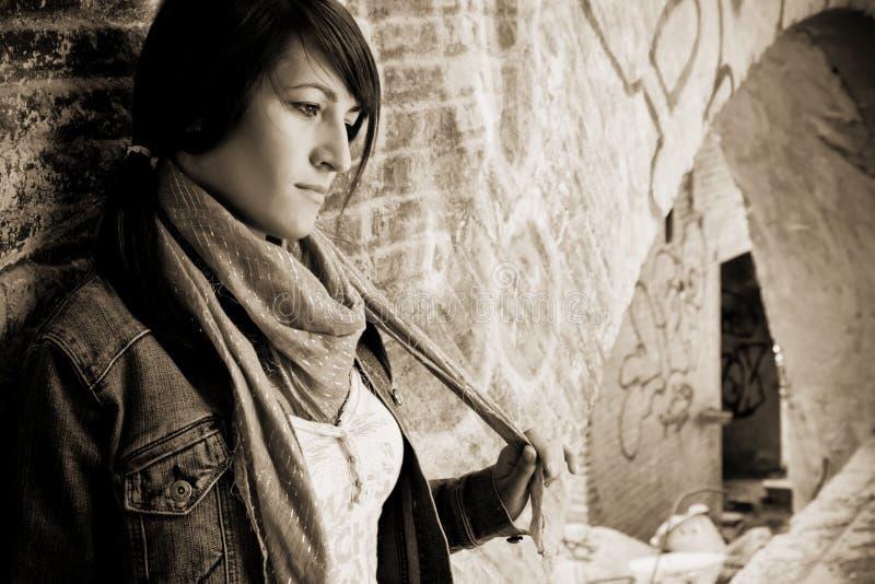 Junge traurige Frau gegen brickwall stockfoto