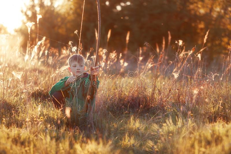 Junge, Trieb mit handgemachtem Pfeil und Bogen am Ziel auf Sonnenuntergang, Sommerzeitfreien lizenzfreie stockbilder