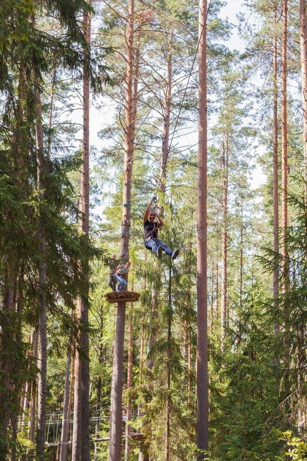 Junge trotzen der Frau, die im Abenteuerseilpark klettert lizenzfreies stockbild