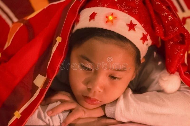Junge trug einen Weihnachtshut unter einem umfassenden, traurig und allein in stockbild