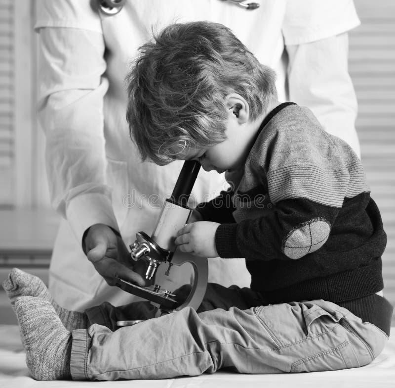 Junge tut Experimente auf hölzernem Hintergrund Mann und Kind mit dem beschäftigten Gesicht, das Doktor oder Wissenschaftler spie stockfotos