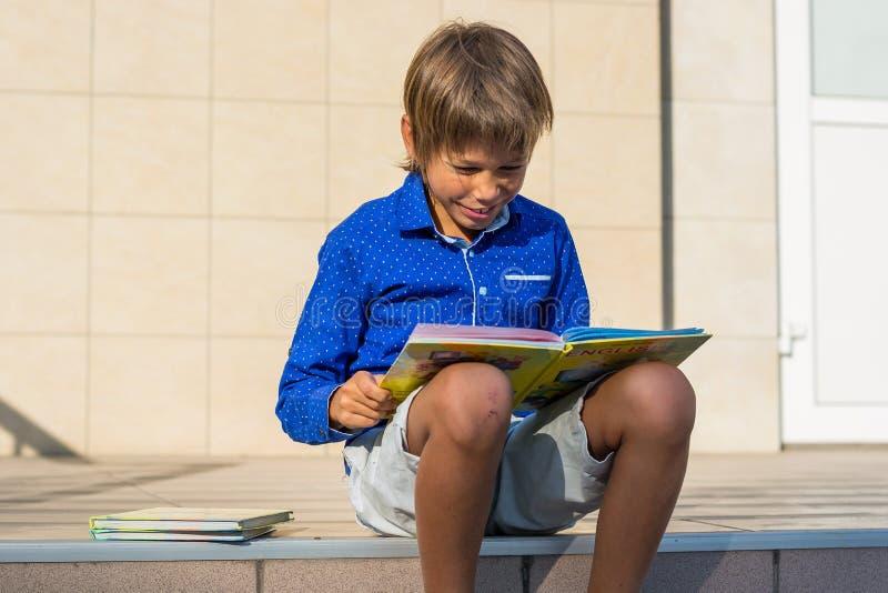Junge-Tyrann sitzt auf den Schritten vor der Schule und liest stockbilder