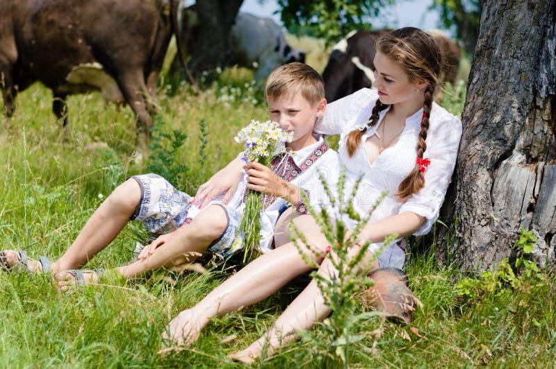 Junge u. schöne junge Frau mit Kühen draußen lizenzfreie stockfotografie