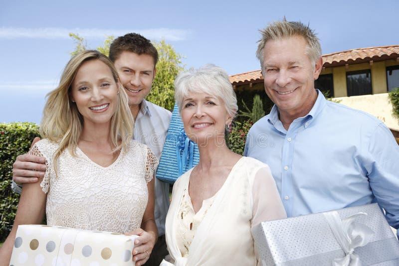 Junge und ältere Paare mit Geschenken draußen lizenzfreie stockfotos