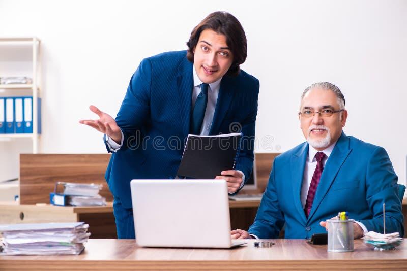 Junge und alte Angestellte, die im Büro zusammenarbeiten stockfotografie