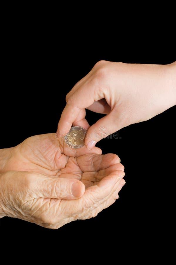Junge und alte Hand mit einer Münze lizenzfreies stockbild