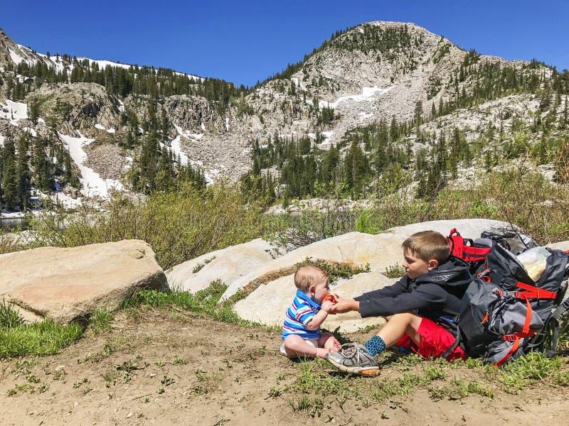 Junge und Baby in den Bergen lizenzfreie stockbilder