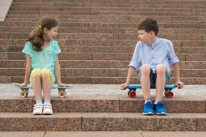Junge und ein Mädchen, das auf den Sportbrettern, streiten an einander sitzt stockbild