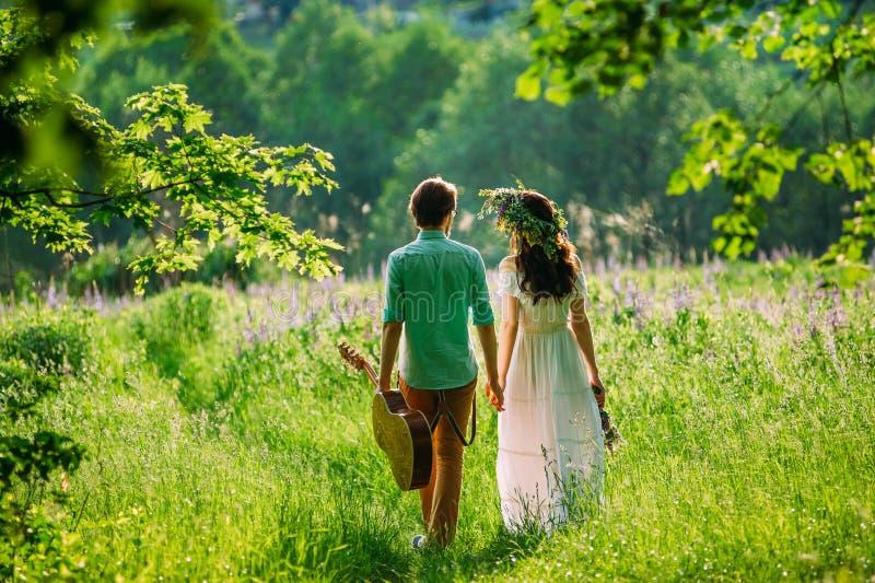 Junge und ein Mädchen in der Liebe gehend in tiefes Gras stockfotos