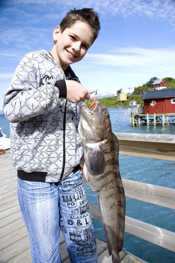 Junge und Fischentrophäe stockfoto