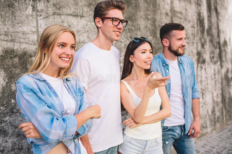 Junge und furchtlose Leute stehen auf grauem Hintergrund und dem Loking direkt Mädchen lächeln Chinesisches Mädchen stockbild