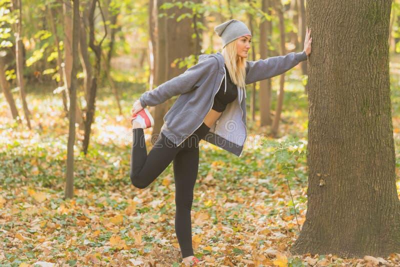 Junge und geeignete erwachsene Frau, die ihre Muskeln im Waldgesunden Lebensstil ausdehnt lizenzfreies stockbild