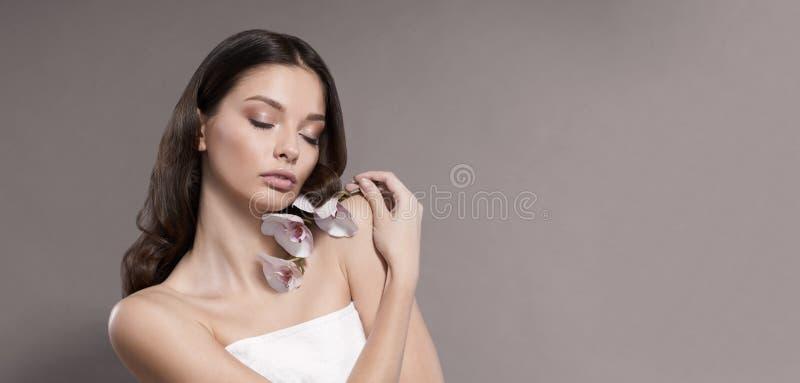 Junge und gesunde Frau mit dem hellen Make-up, das Orchideenblume hält Beige Hintergrund stockbild
