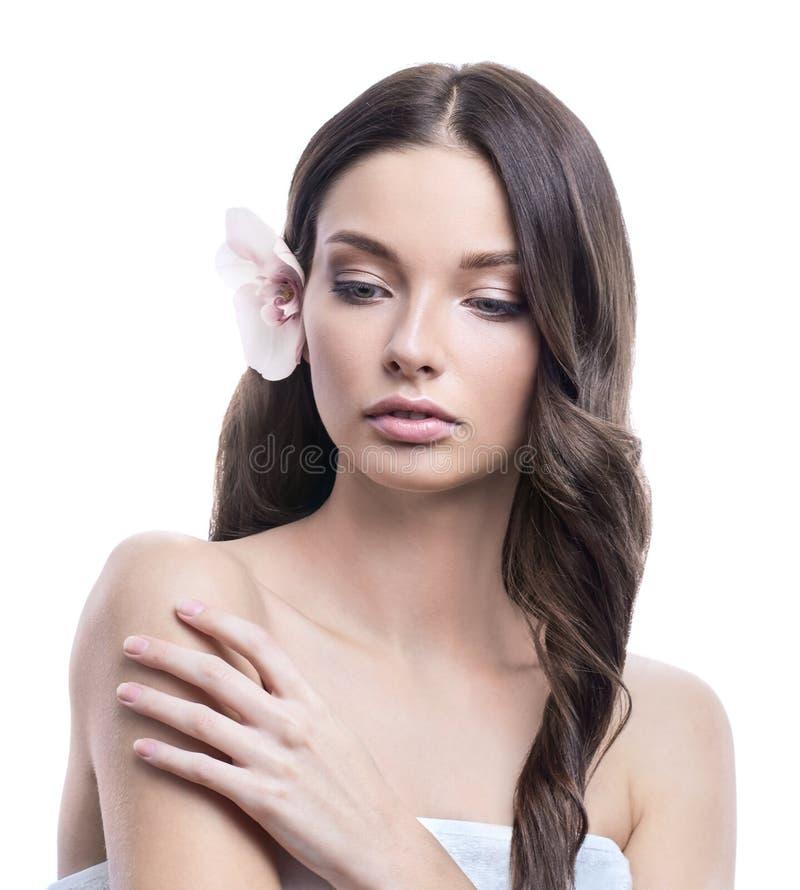Junge und gesunde Frau mit hellem Make-up auf weißem Hintergrund Das Haar wird mit schöner Orchideenblume verziert stockbild