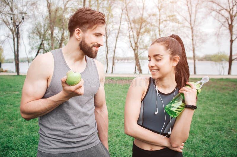 Junge und gesunde Paare sind miteinander stehend und schauend und lächelnd Er isst einen Apfel Mädchen hat a lizenzfreie stockfotos