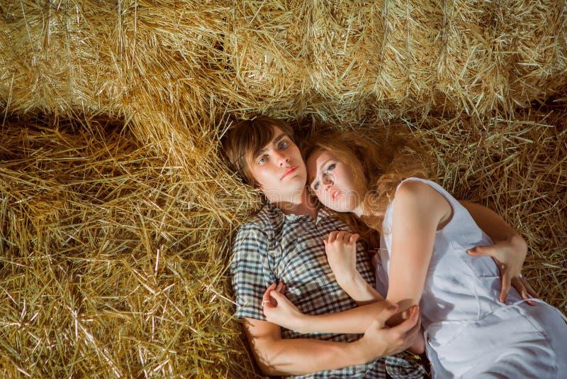 Junge und gil lyingYoung Junge und gyrl, die im Heu liegen Sommerporträt im Freien von schönen Paaren im Heu Sommer portr im Frei stockfotografie