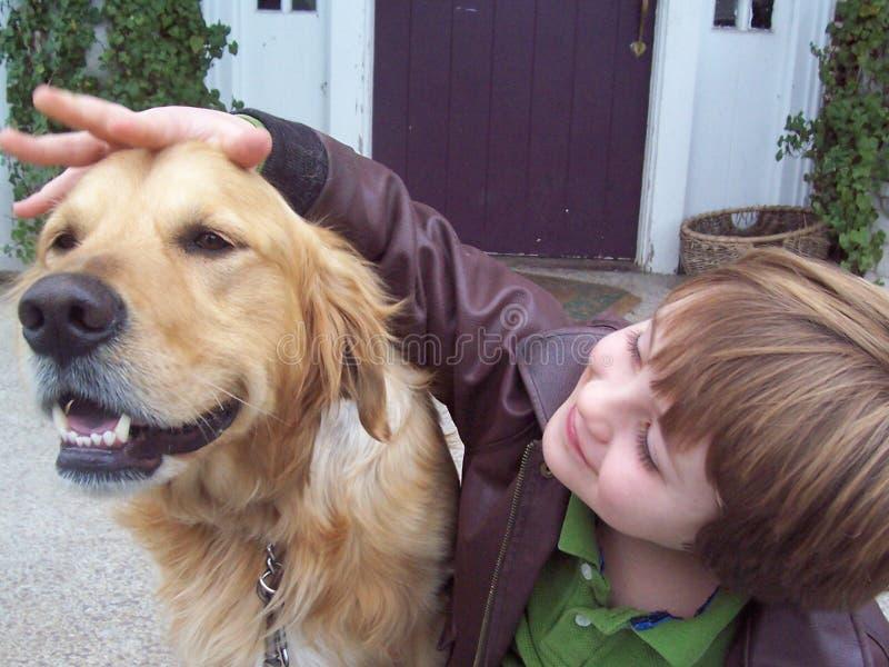 Junge und goldener Apportierhund auf Portal lizenzfreies stockbild