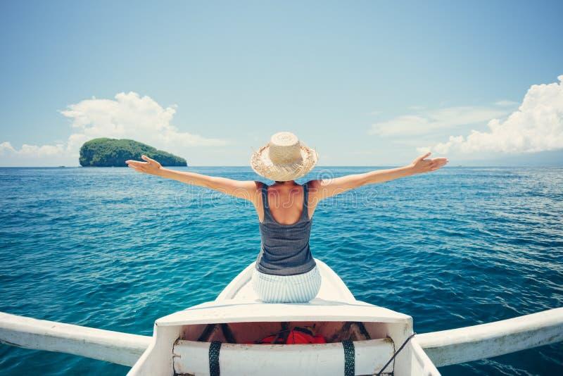 Junge und hübsche Frau, die auf das Boot im Ozean allein reist lizenzfreie stockbilder