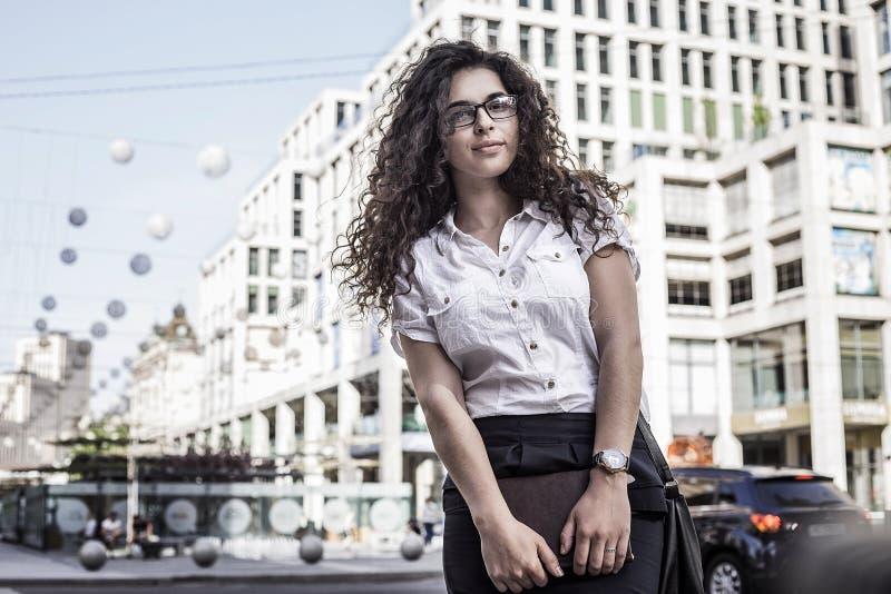 Junge und hübsche Frau, die auf dem Stadthintergrund steht stockfotos