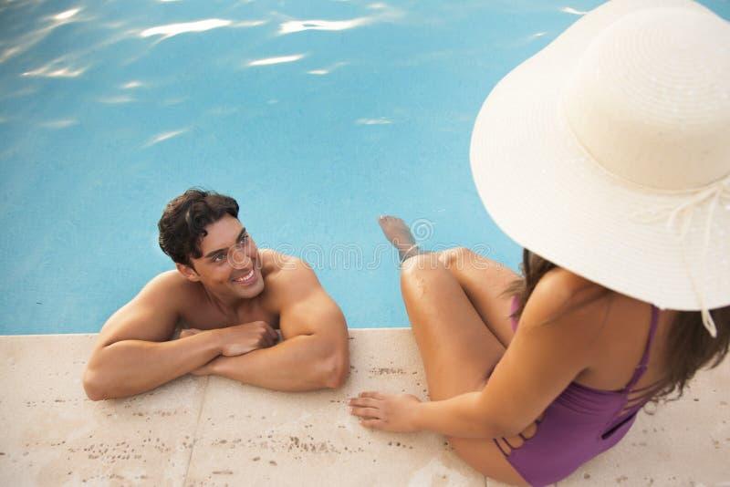 Junge und hübsche Paare, die das Hotelpool genießen stockfotos