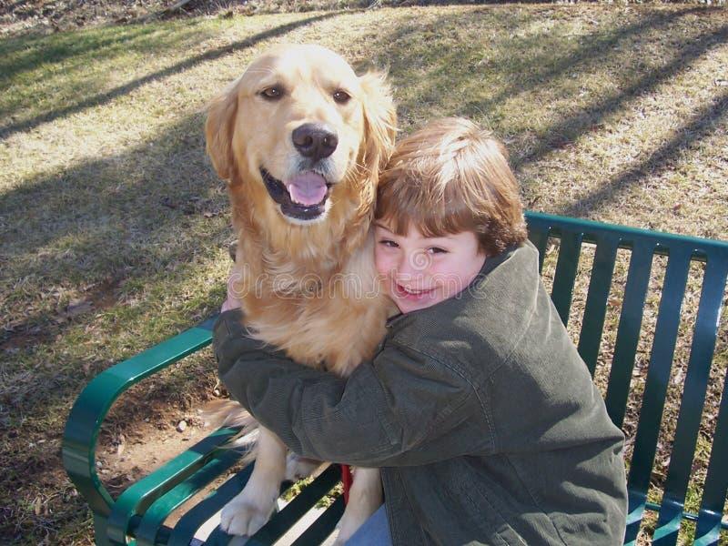 Junge und Hund auf Bank lizenzfreie stockfotografie