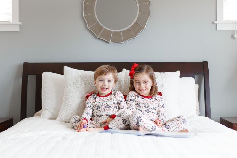 Junge und Mädchen auf Bett mit Weihnachtspyjamas lizenzfreies stockfoto