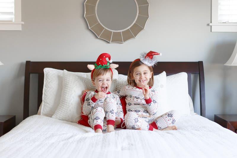 Junge und Mädchen auf Bett mit Weihnachtspyjamas lizenzfreie stockfotografie