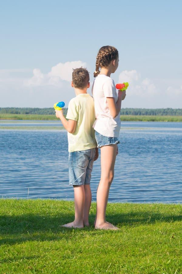 Junge und Mädchen auf dem See, Wasserpistolen halten und mit ihren Rückseiten, gegen eine schöne Landschaft miteinander stehen un lizenzfreie stockfotografie