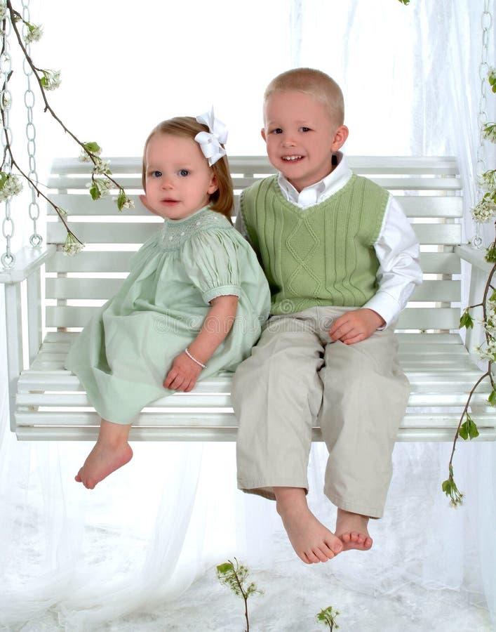 Junge und Mädchen auf Schwingen lizenzfreie stockfotografie