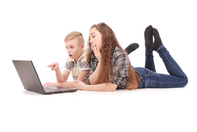 Junge und Mädchen, das einen Laptop liegt auf dem Boden verwendet stockfoto