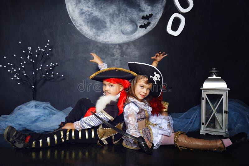 Junge und Mädchen in den Piratenkostümen Ein grimmiger Minireaper, der eine Sense anhält, steht auf einem Kalendertag, der glückl lizenzfreies stockfoto