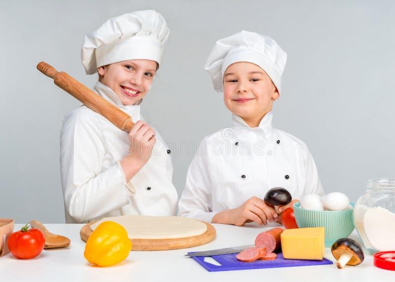 Junge und Mädchen in der weißen Uniform durch die Tabelle bereiten Pizza zu stockfoto