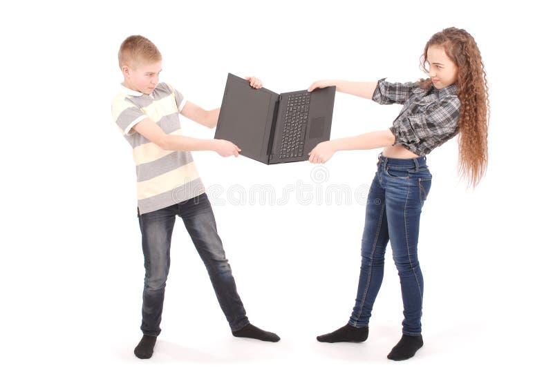 Junge und Mädchen, die über einem Laptop kämpfen lizenzfreie stockfotos