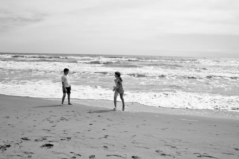 Junge und Mädchen, die auf beatch vor Meer laufen und spielen Sepi lizenzfreie stockfotos