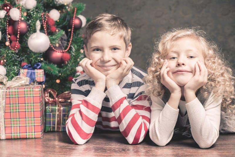 Junge und Mädchen, die auf dem Boden unter Weihnachtsbaum liegen stockbilder