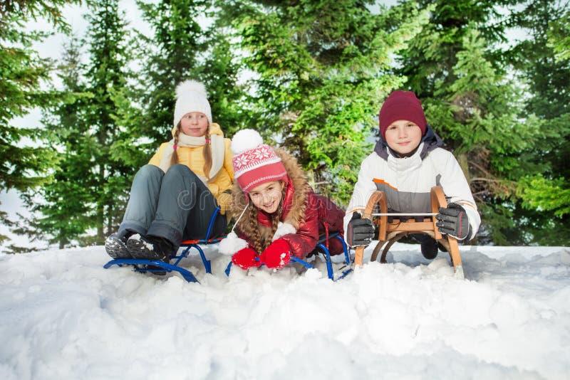 Junge und Mädchen, die auf ihrem Schlitten an den Hügeln sitzen lizenzfreies stockbild