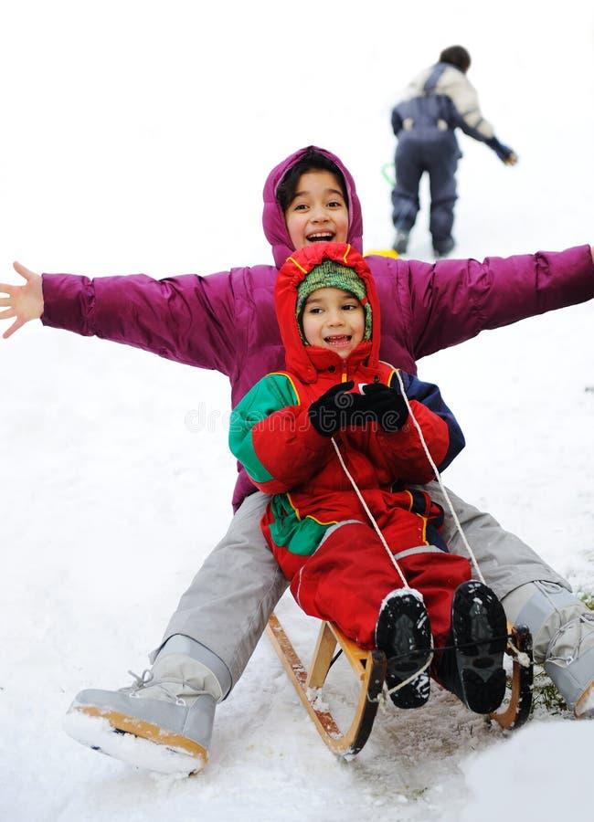 Junge und Mädchen, die auf Schnee sledging sind lizenzfreie stockbilder