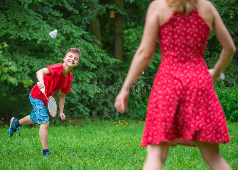 Junge und Mädchen, die Badminton spielen stockbild