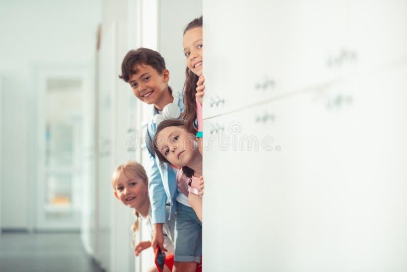 Junge und Mädchen, die bei nahe Bruch der Schließfächer in der Schule stehen lächeln lizenzfreies stockfoto