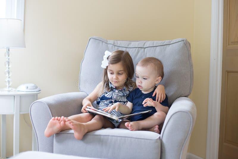 Junge und Mädchen, die ein Buch lesen stockfotografie