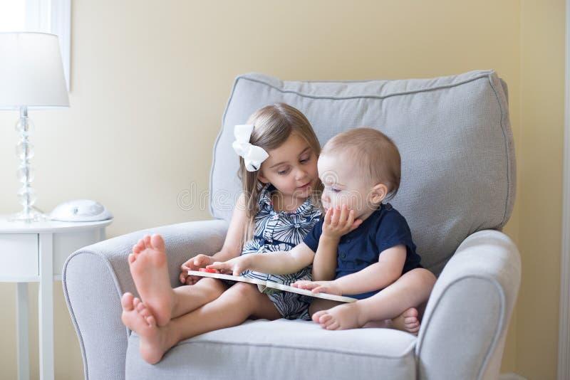 Junge und Mädchen, die ein Buch lesen lizenzfreies stockbild