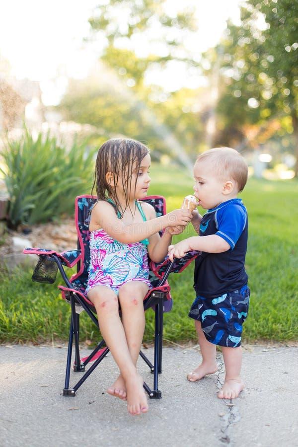 Junge und Mädchen, die Eiscreme essen stockbild