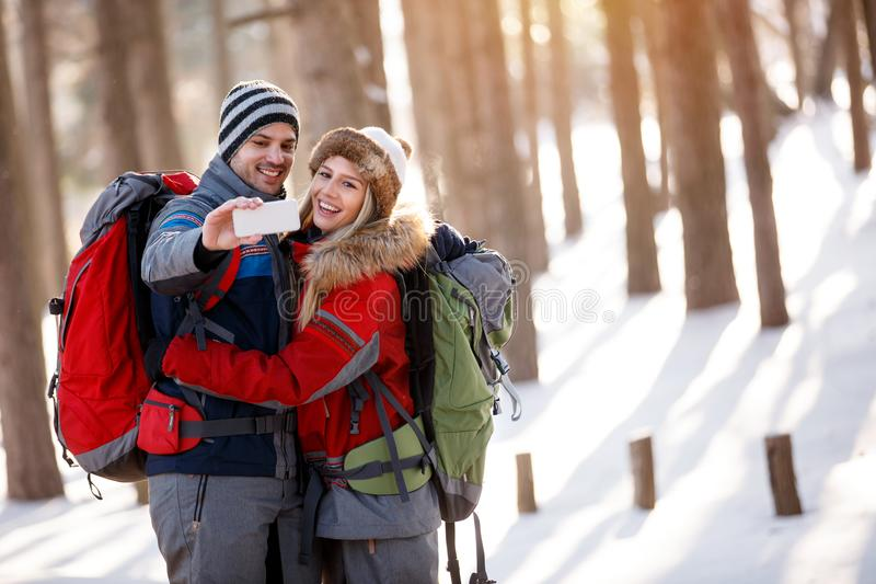 Junge und Mädchen, die Foto in der schneebedeckten Natur machen stockfoto