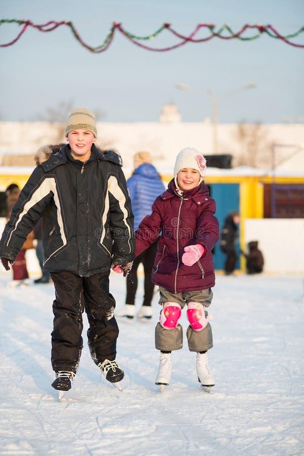 Junge und Mädchen, die Hand in Hand auf Eisbahn eislaufen stockfoto