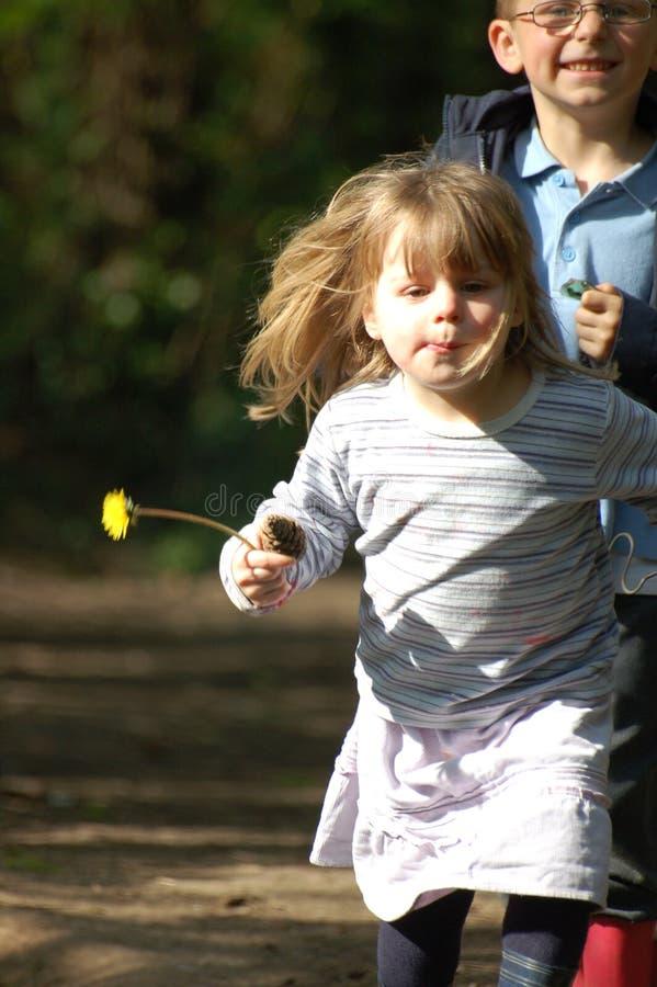 Junge und Mädchen, die in Holz laufen stockfotos