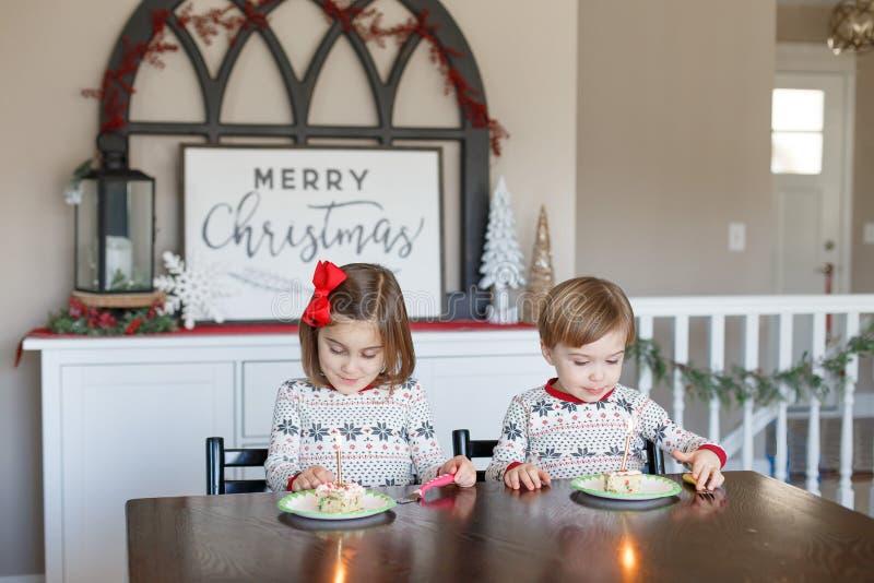 Junge und Mädchen, die Kuchen für Weihnachten essen lizenzfreie stockbilder