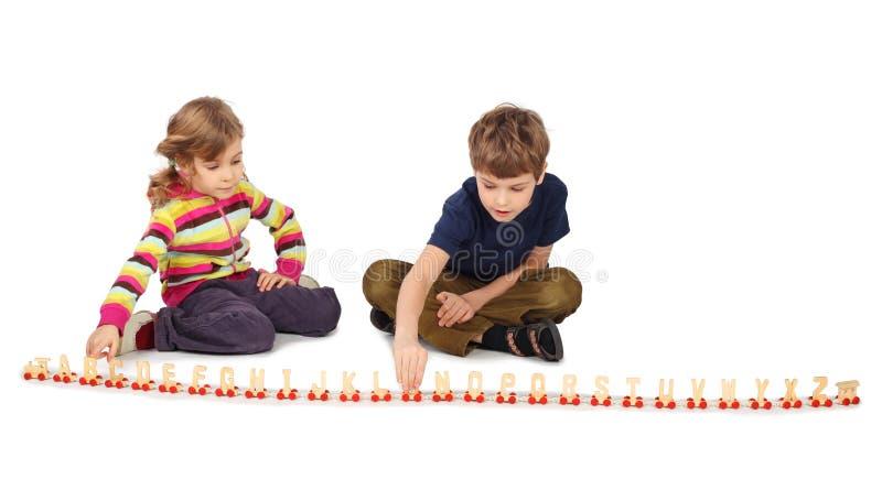 Junge und Mädchen, die mit hölzernem Gleis spielen lizenzfreies stockbild