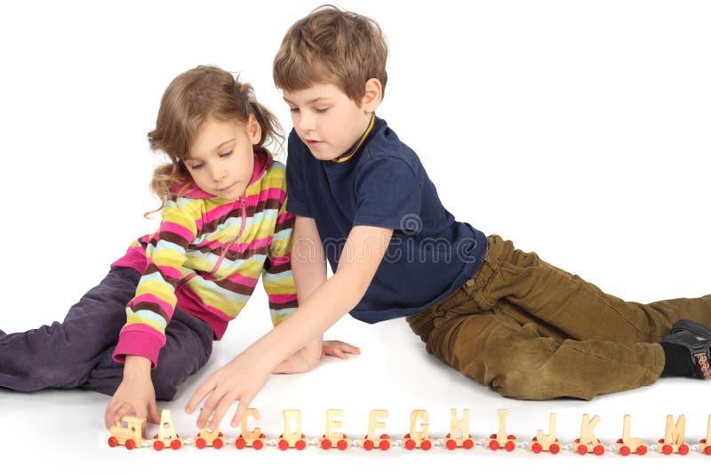 Junge und Mädchen, die mit hölzernem Gleis spielen lizenzfreie stockfotografie