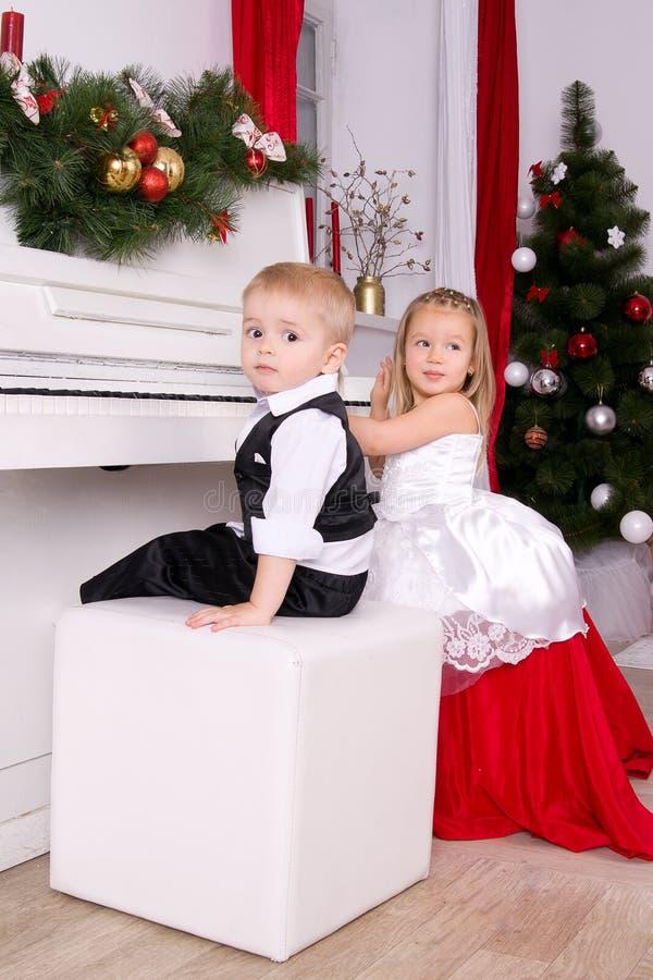 Junge und Mädchen, die nahe weißem Klavier sitzen lizenzfreie stockfotos