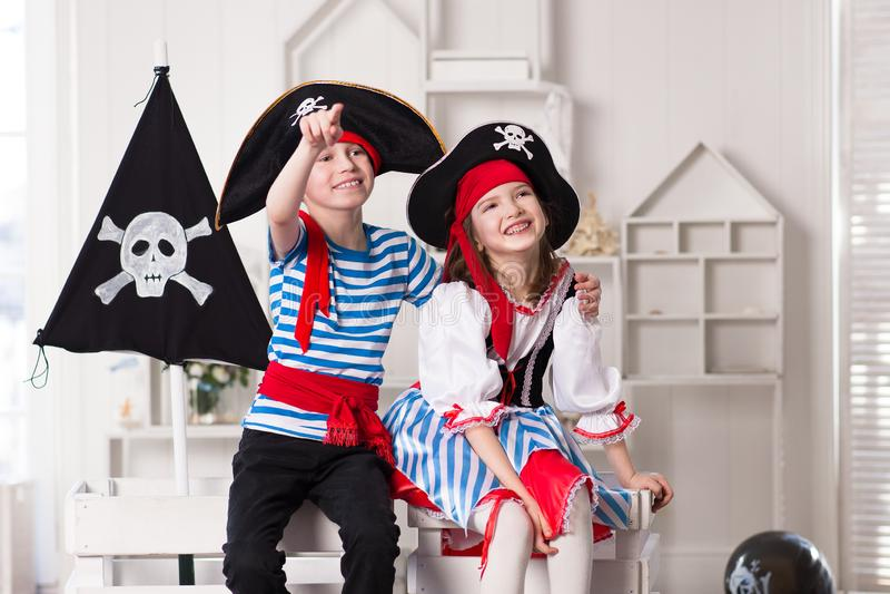 Junge und Mädchen, die Piraten spielen Sie tragen Piratenkostüme stockbilder
